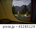 View from inside tourist tent at sunset. Alone tourist, man hiker sitting at bonfire 45285129