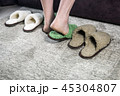 feet in green soft Slippers on the carpet in the room  45304807