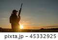 Silhouette of a woman with a rifle. It stands in a picturesque place at sunset. Sports shooting and 45332925