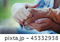 A young woman holds an elderly lady's hand. Granddaughter holds the hand of his baushka in his hands 45332938