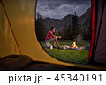 View from inside tourist tent at sunset. Alone tourist, man hiker sitting at bonfire 45340191