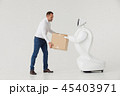 Modern Robotic Technologies. A man communicates with a robot, with cardboard box in hand. 45403971