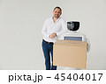Modern Robotic Technologies. A man communicates with a robot, with cardboard box in hand. 45404017
