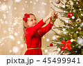 happy girl in red dress decorating christmas tree 45499941