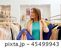 happy young woman choosing clothes in mall 45499943