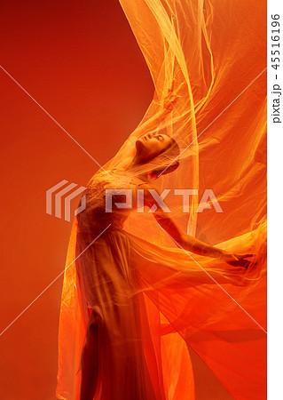 Ballerina. Young graceful female ballet dancer dancing over red studio. Beauty of classic ballet. 45516196