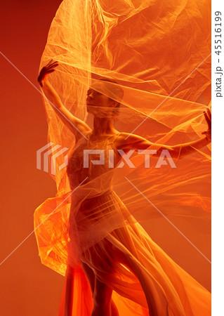 Ballerina. Young graceful female ballet dancer dancing over red studio. Beauty of classic ballet. 45516199