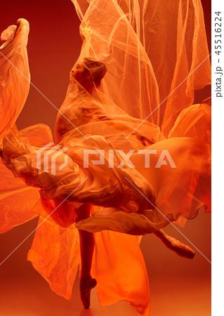 Ballerina. Young graceful female ballet dancer dancing over red studio. Beauty of classic ballet. 45516224