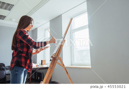 Young woman artist painting a picture in studio 45553021