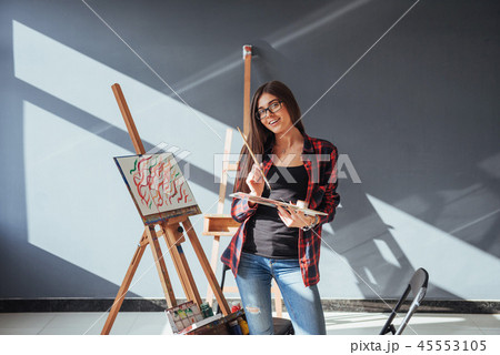 Pretty Pretty Girl artist paints on canvas painting on the easel. 45553105
