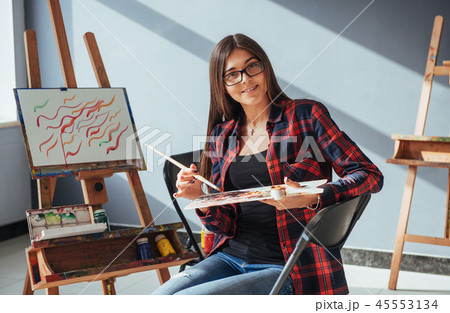 Pretty Pretty Girl artist paints on canvas painting on the easel. 45553134