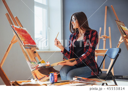 Dark-haired artist holding a brush in his hand and draws a picture on canvas. Thinks that draw on 45553814