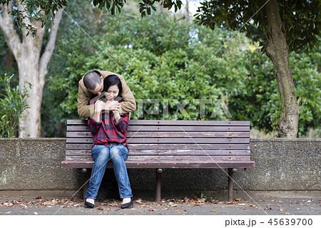 公園のベンチでハグをするカップル 45639700