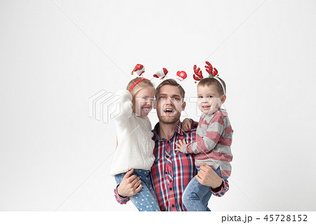 Father holds children in his arms on a white background. Happy family in funny Christmas headbands. 45728152
