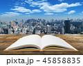 木目の机に置かれた白紙の本と青空とビジネス都市風景の背景 45858835