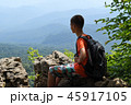 Boy sitting on edge of cliff with backpack 45917105