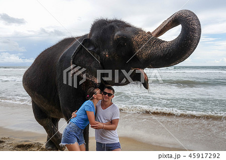 Portrait of a happy young couple with an elephant 45917292
