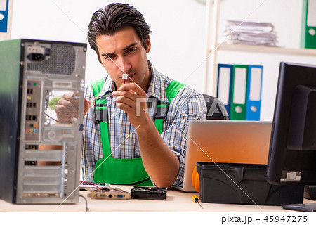Young engineer repairing broken computer at the office  45947275