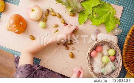 Little girl sitting at the desk makes necklace of acorns 45982187