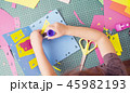 Hands of little girl gluing colored paper 45982193