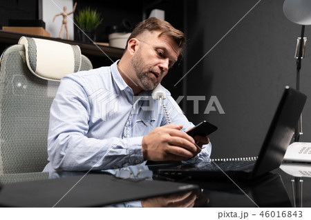 young man sitting at computer Desk and holding landline phone and mobile phone 46016843