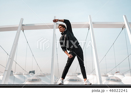 Young man is doing warming up exercises near the stadium 46022241