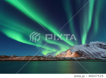Aurora borealis above the snow covered mountain 46047529