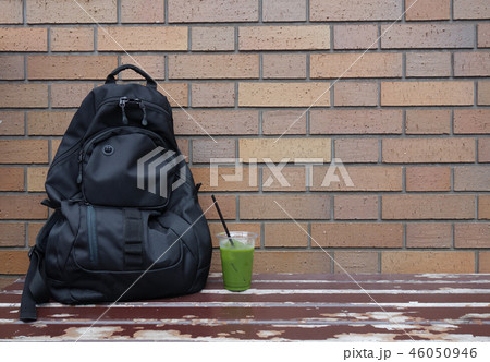 黒いリュックと緑茶 レンガ 休憩 Black backpack and green tea 46050946