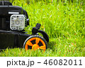 Fragment of grass mower standing on fresh lawn 46082011