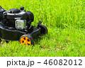 Grass mower stands on green lawn in summer garden 46082012