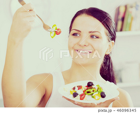 Woman holding fork and plate 46096345