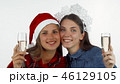 Beautiful Christmas women friends holding champagne glasses, smiling happily 46129105