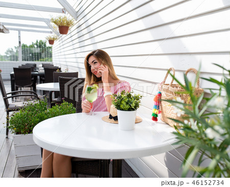 The girl sits in a cafe at a table. In summer in city on a sunny day in fresh air. Talking on phone 46152734