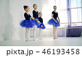 Ballet lesson with a female coach instructing little girls 46193458