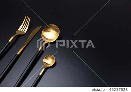 Set of black and gold cutlery on black background 46237628
