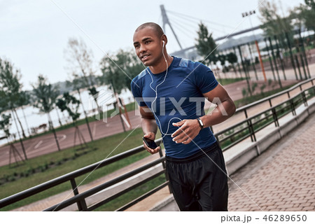 Side view of young active african man with headphones jogging outdoors 46289650