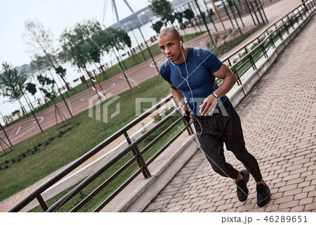 Full length of young active african man with headphones jogging outdoors 46289651