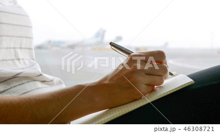 Young woman writing in diary at airport, close-up 46308721