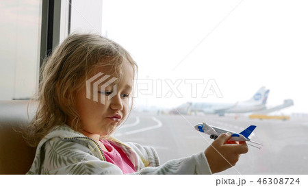 Cute child girl playing with toy airplane in airport terminal 46308724