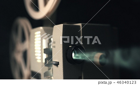 Front view of an old-fashioned antique Super 8mm film projector, projecting a beam of light in a 46340123