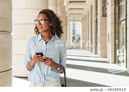 Woman standing at office building 46380919