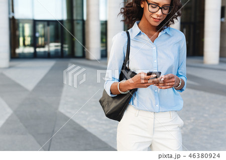 African woman walking outside with smartphone 46380924