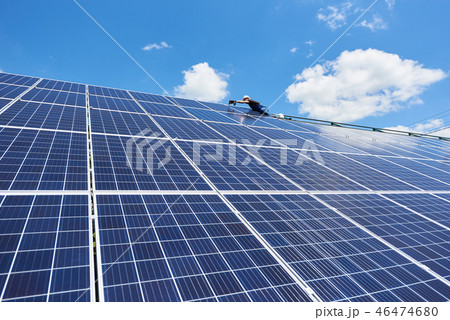 Professional worker installing solar panels on the green metal construction 46474680