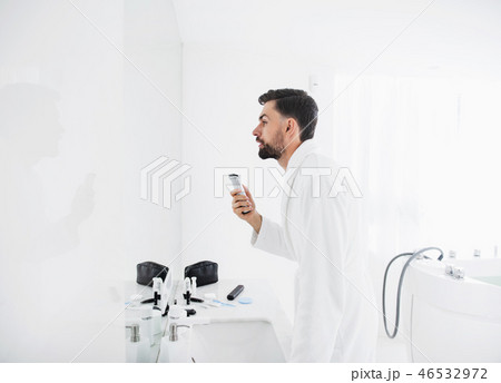 Waist up of serious man standing in front of the mirror 46532972