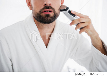 Close up of the man shaving his face with shaving machine 46532985