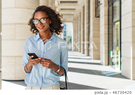 Pretty smiling woman standing outside with phone 46730420