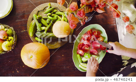 Senior female hands cutting tomatoes and cucumbers 46740241
