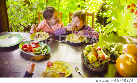 Two girls are sitting at the table in the garden 46740874