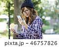 公園でスマホを見る女性  46757826