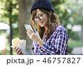 公園でスマホを見る女性  46757827